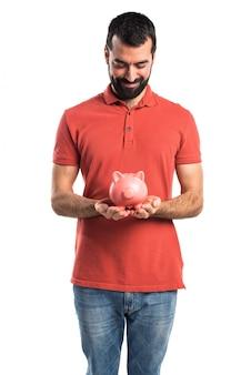 Handsome mann hält ein sparschwein