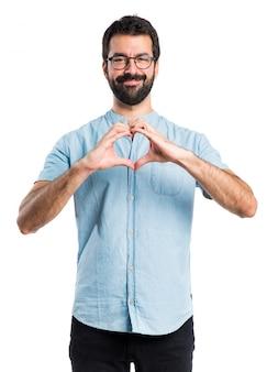 Handsome mann mit blauen gläser machen ein herz mit den händen