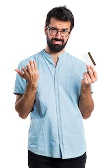 Handsome mann mit blauen gläser mit einer kreditkarte