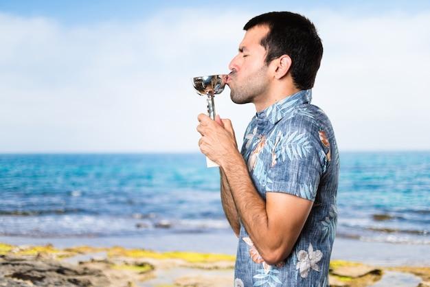 Handsome mann mit blumen-shirt mit einer trophäe am strand