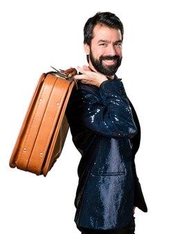 Handsome mann mit paillettenjacke mit einem vintage aktenkoffer