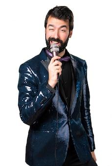 Handsome mann mit paillettenjacke singen mit mikrofon