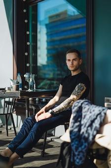 Handsome tätowierte mann auf einer sommerterrasse in einem stadtcafé trinkt wein. straße cafe.