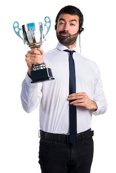 Handsome telemarketer mann hält eine trophäe