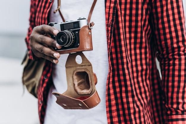 Handsome und glücklich afro american tourist mit alten kamera in der modernen stadt