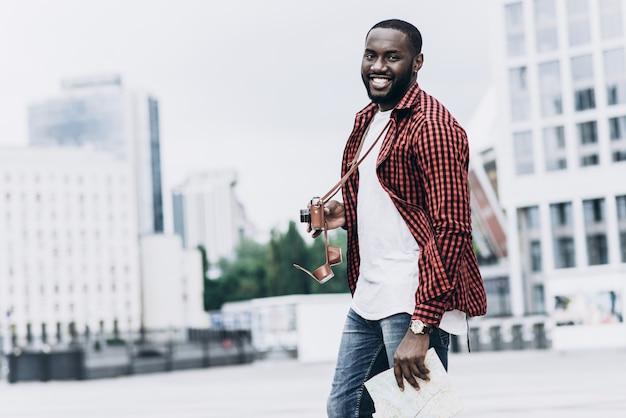 Handsome und glücklich afro american tourist mit alten kamera und karte in der modernen stadt