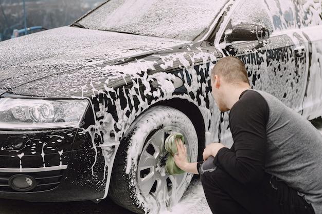 Handsomen mann in einem schwarzen pullover, der sein auto wäscht