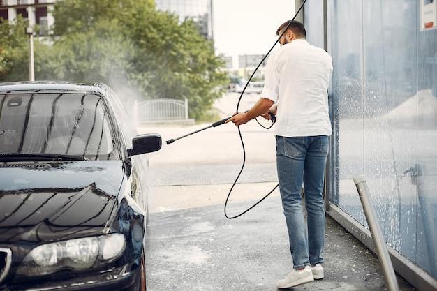 Handsomen mann in einem weißen hemd, das sein auto wäscht