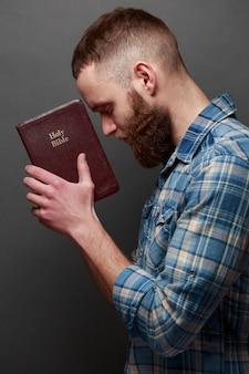 Handsone mann, der über bibel in einem dunklen raum über grauer beschaffenheit liest und betet