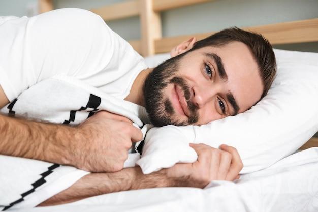 Handsonme lächelnder mann, der auf einem kissen im bett schläft