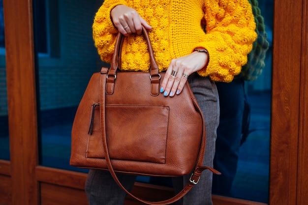 Handtasche. frau, die stilvolle tasche hält und gelbe strickjacke trägt.