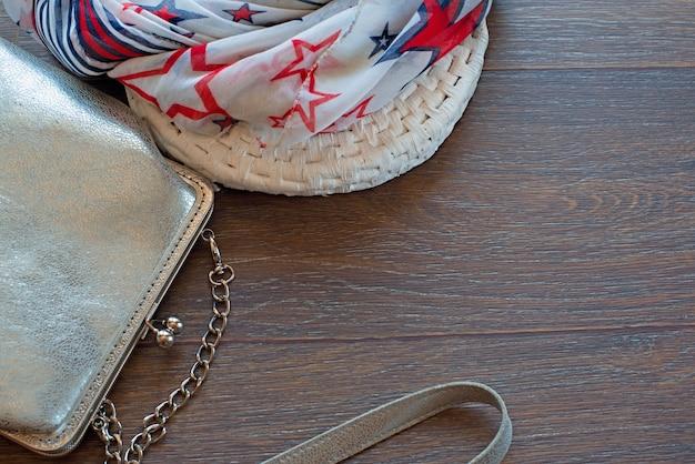 Handtasche für frauen und leichtes tuch auf einem hölzernen dunklen hintergrund.