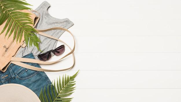 Handtasche in der nähe von sonnenbrillen mit abnutzung und pflanzenzweigen