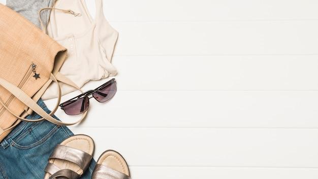 Handtasche in der nähe von sonnenbrillen mit verschleiß und schuhen