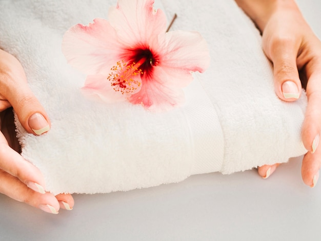 Handtuch in der hand gehalten mit blume an der spitze