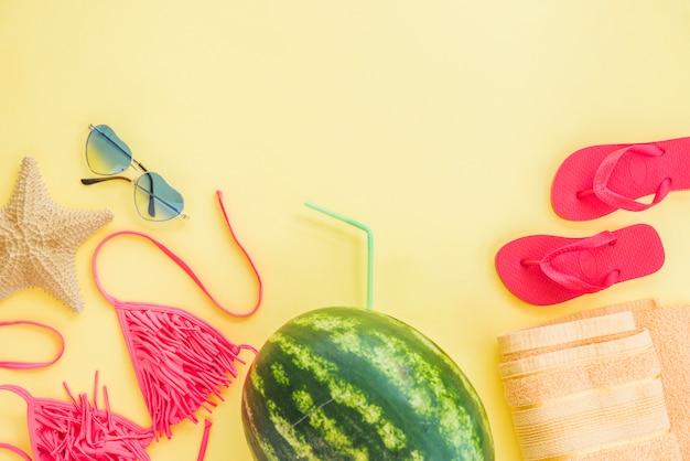 Handtuch in der nähe von flip-flops mit wassermelone und badeanzug
