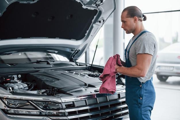 Handtuch in händen. mann in blauer uniform arbeitet mit kaputtem auto. reparaturen durchführen