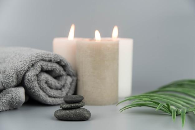Handtuch mit aromatischen kerzen, flasche mit natürlichen organischen ätherischen ölen