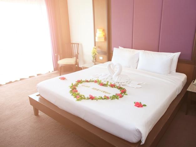 Handtuchschwäne geformt auf luxusbett, honigmondbett