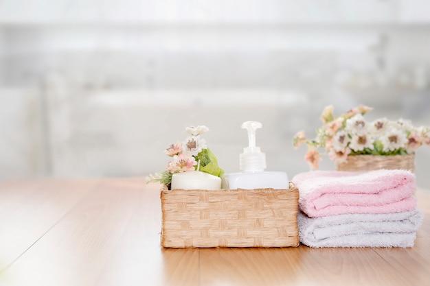 Handtücher auf holztisch mit kopierraum auf verschwommenem badezimmer.