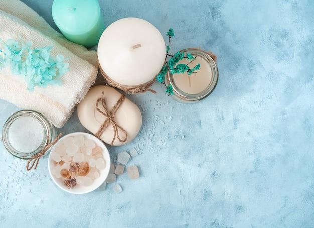 Handtücher, kerzen und reinigungsmittel auf einem cyanidhintergrund. draufsicht mit platz zum kopieren. das konzept eines gesunden lebensstils.