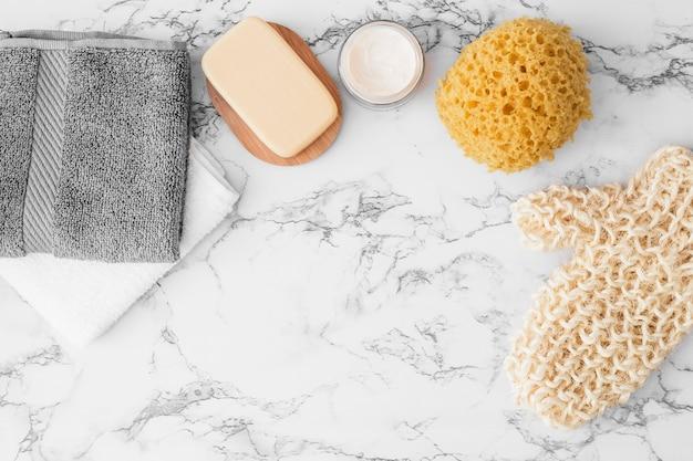 Handtücher; seife; feuchtigkeitscreme; schwamm und peelinghandschuh auf marmor