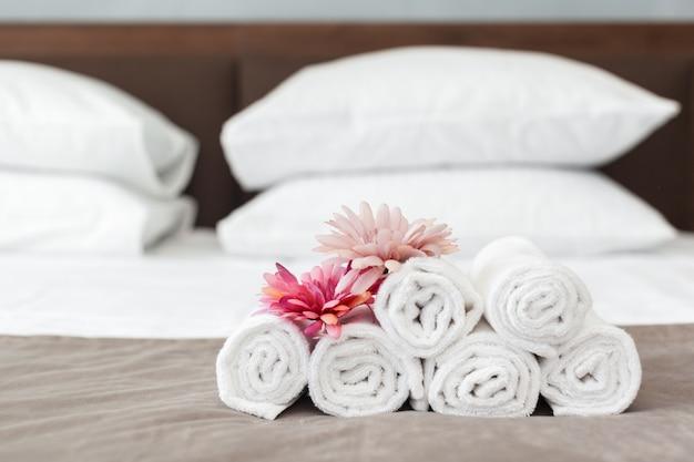 Handtücher und blumen auf dem bett im hotelzimmer