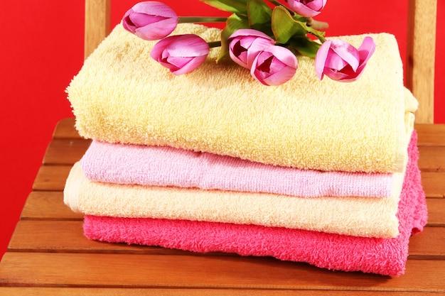 Handtücher und blumen auf holzstuhl auf roter oberfläche