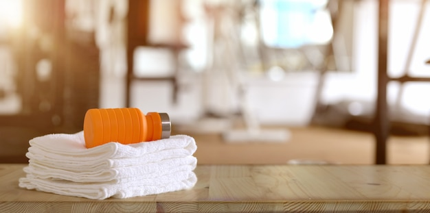 Handtücher und orange sportflasche mit fitnessraum