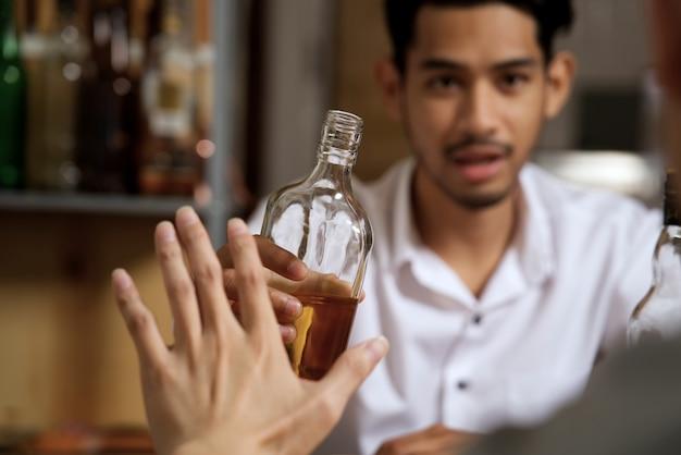 Handverweigerungsalkohol vom mann, der gegenüberliegende seite sitzt.