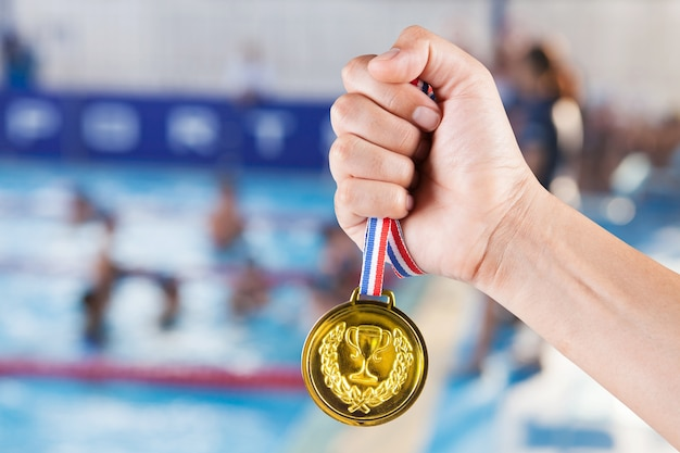 Handvoll asiatischen mann mit goldmedaille mit verschwommenen hintergrund von schwimmbad und schwimmen wettbewerb.
