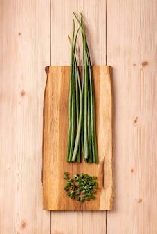 Handvoll gehackte grüne zwiebel und zwiebelstiele auf holzbrett auf tisch, draufsicht.