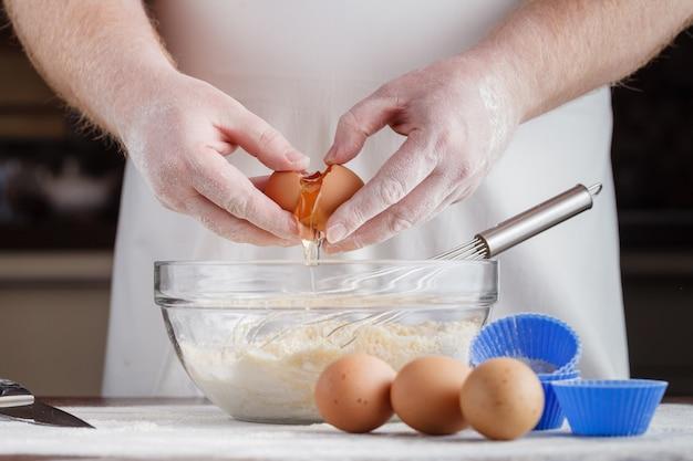 Handvoll mehl mit ei auf einer rustikalen küche.