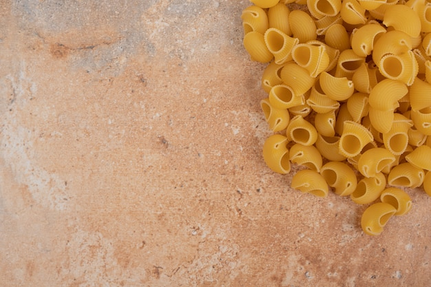 Handvoll rohe unvorbereitete nudeln auf marmorhintergrund. hochwertiges foto