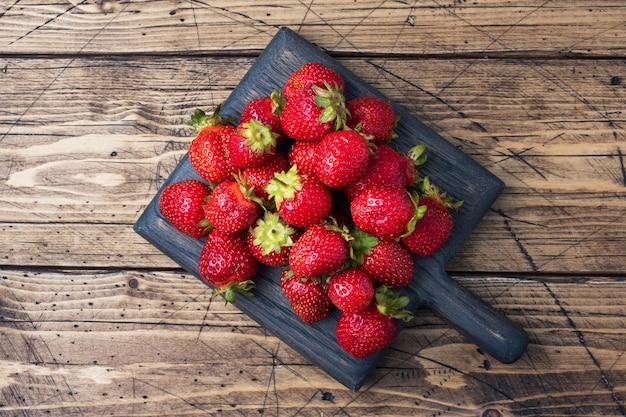 Handvoll saftige reife erdbeeren auf einem rustikalen holzhintergrund. süßes gesundes dessert, vitaminernte. platz kopieren.