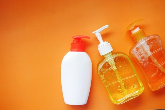 Handwaschflüssigkeit in einem behälter auf orangem hintergrund