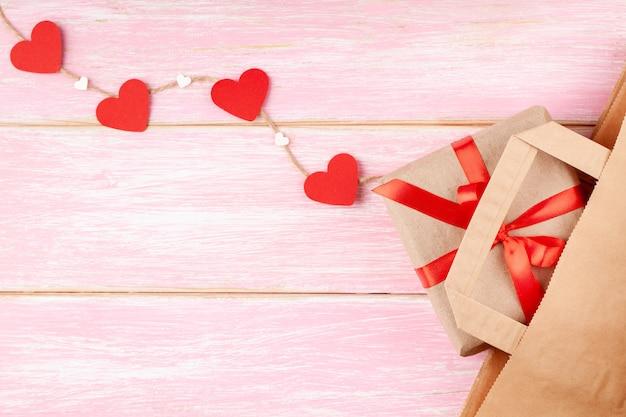 Handwerk papiertüte und geschenkbox mit roter schleife und herzen
