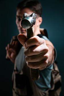 Handwerker arbeiter hält hammer posiert vor der kamera über blau. bauwerkzeug-konzept