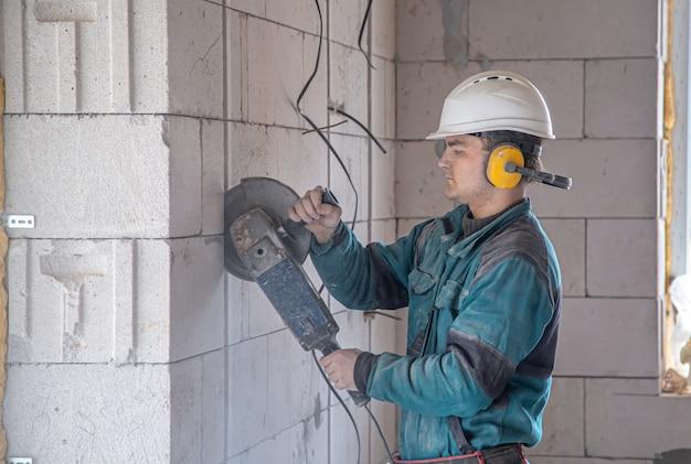 Handwerker auf einer baustelle beim schneiden mit einer mühle.