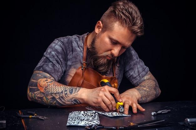 Handwerker aus leder, der in seinem lederstudio lederwerkstücke herstellt