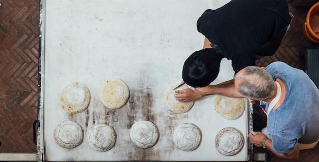 Handwerker bäcker lehrt seinen lehrling, hefebrotteig zu schneiden