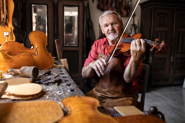 Handwerker, der die qualität überprüft und in seiner altmodischen tischlerwerkstatt geige spielt