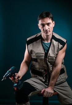 Handwerker, der elektrische bohrmaschine hält, die zur kamera über blau aufwirft. bauwerkzeug-konzept