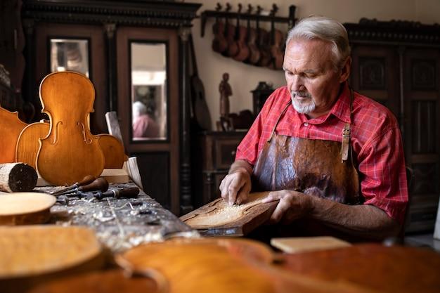 Handwerker, der holz schnitzt, um geigenmusikinstrument zu schaffen