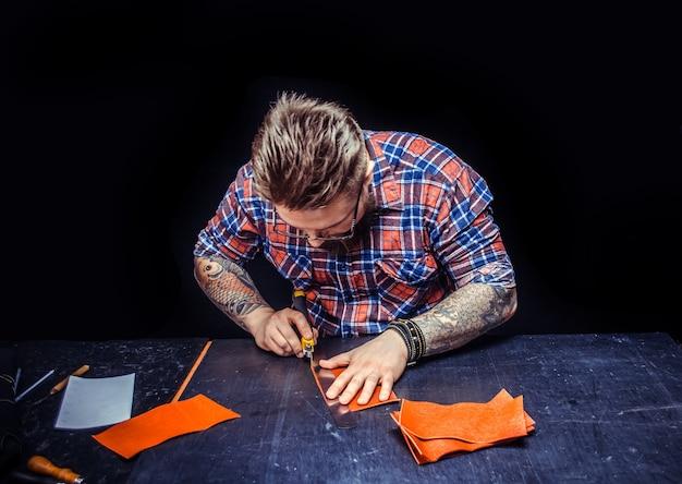 Handwerker, der im gerbergeschäft ein neues lederprodukt herstellt