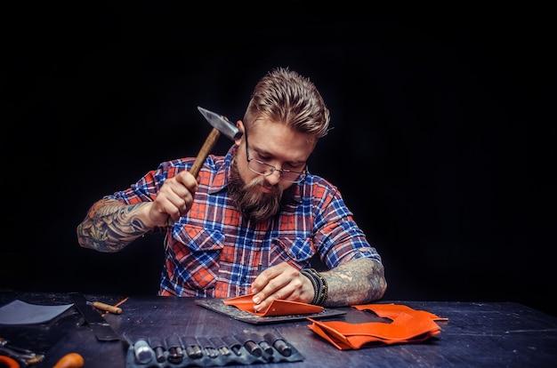 Handwerker, der in seiner gerberei neue lederprodukte herstellt.
