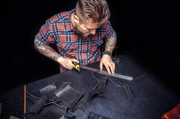 Handwerker, der lederumrisse für seine neue produktion am arbeitsplatz schneidet. / handwerker, der mit leder arbeitet, verarbeitet ein werkstück aus leder im geschäft.