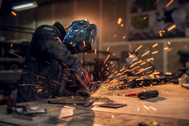 Handwerker, der metall sägt, funkelt in der werkstatt