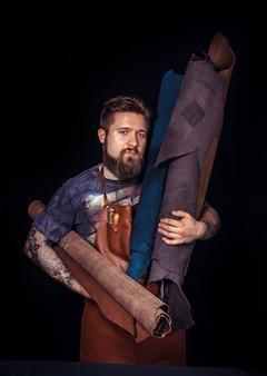 Handwerker, der mit leder arbeitet und lederarbeiten am werkregal herstellt.