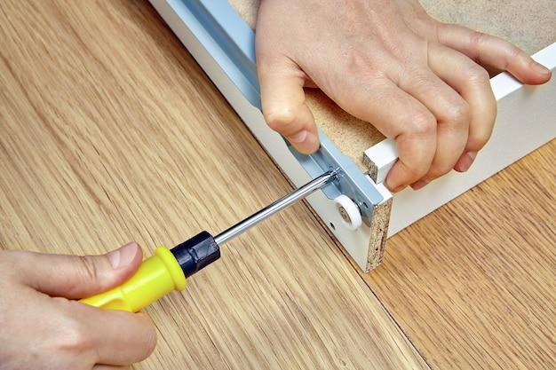 Handwerker, der möbel mit handschraubendreher zusammenbaut, zieht schrauben an der seite der schublade fest.